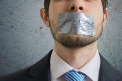 Zwei Geschäftsleute getrennt auf weißem Hintergrund Mann wird mit Klebstreifen auf seinem Mund zum Schweigen gebracht Lizenzfreie Stockfotos