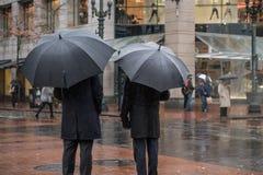 Zwei Geschäftsleute unter Regenschirmen im Regen in einer städtischen Landschaft Lizenzfreies Stockbild