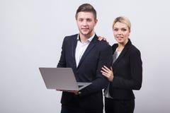 Zwei Geschäftsmänner der Mann und die Frau mit einem Laptop in der Hand auf einem whi Stockbild