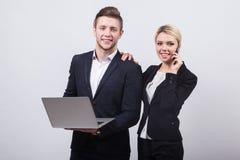 Zwei Geschäftsmänner der Mann und die Frau mit einem Laptop in der Hand auf einem whi Lizenzfreies Stockbild