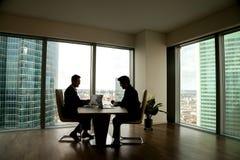 Zwei Geschäftsmänner, die über das Sitzen am Konferenztische im moder verhandeln stockfotos