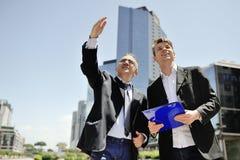 Zwei Geschäftsmänner, die über ein neues Projekt auf Hintergrundbürogebäuden arbeiten Stockfoto
