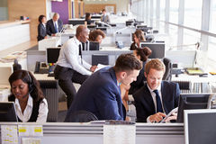 Zwei Geschäftsmänner, die Arbeit in einem beschäftigten, Bürogroßraum besprechen stockfotografie