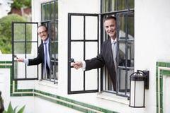 Zwei Geschäftsmänner, die aus einem Fenster heraus schauen Stockbild