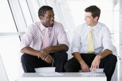 Zwei Geschäftsmänner, die bei der Bürovorhalleunterhaltung sitzen Lizenzfreie Stockbilder