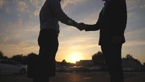 Zwei Geschäftsmänner, die in der städtischen Umwelt bei Sonnenuntergang sich grüßen Geschäftshändedruck im Freien Rütteln von män stock footage