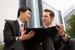Zwei Geschäftsmänner, die Dokument außerhalb des Büros behandeln Lizenzfreies Stockbild