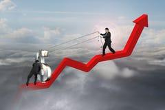 Zwei Geschäftsmänner, die Dollarzeichen aufwärts auf roter Trendlinie bewegen Stockbild