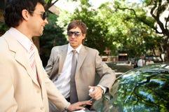 Geschäftsmänner, die um Auto sich treffen. Stockfotografie