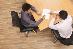 Zwei Geschäftsmänner, die einen Vertrag am Tisch, obenliegender Schuss sitzen und unterzeichnen stockfoto