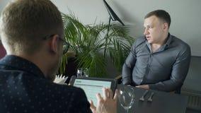 Zwei Geschäftsmänner, die Finanzierung auf der Tablette sitzt während des Mittagessens besprechen stock footage