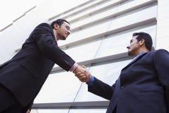 Zwei Geschäftsmänner, die Hände außerhalb des Bürobaus rütteln Lizenzfreie Stockfotografie