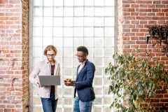 Zwei Geschäftsmänner, die im Dachbodenbüro stehen stockfotos