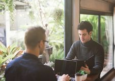 Zwei Geschäftsmänner, die Laptop bei der Sitzung in der Kaffeestube verwenden stockfotografie