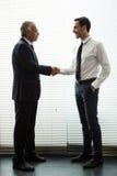 Zwei Geschäftsmänner, die oben stehen und Hände rütteln Stockbilder