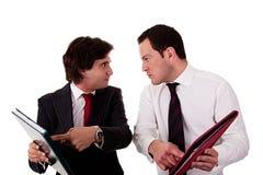 Zwei Geschäftsmänner, die wegen der Arbeit, pointi behandeln Stockfotografie