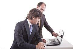 Zwei Geschäftsmänner, die zusammen an einem Laptop arbeiten Lizenzfreie Stockfotos