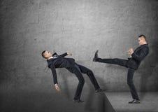 Zwei Geschäftsmänner, einer, der den anderen in den Abstand im Boden, alle auf dem grauen Hintergrund tritt Stockbilder