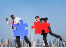 Zwei Geschäftsmänner in einer städtischen Szene mit Puzzlespiel Lizenzfreies Stockbild