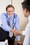 Zwei Geschäftsmänner im Büro, das Hände rüttelt Stockbild