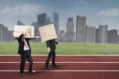 Zwei Geschäftsmänner mit Pappe auf der Bahn Stockfoto