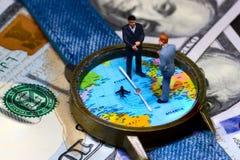 Zwei Geschäftsmannfigürchen rechtzeitig und Geldhintergrund Weltweites Geschäftskonzept stockfotos