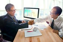 Zwei Geschäftsmannpartner, der Hand mit Glückgefühl achtern rüttelt Stockfoto