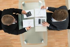 Zwei Geschäftsmannrechenrechnungen unter Verwendung des Taschenrechners Stockfoto
