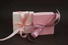 Zwei Geschenkboxen mit einem rosa Bogen lokalisiert auf braunem Hintergrund Geschenk, Geburtstag Verkaufskonzept - Hand mit Vergr Stockfotos