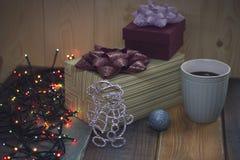 Zwei Geschenkboxen, Weihnachten spielt, ein Tasse Kaffee auf dem tablen Stockfotos