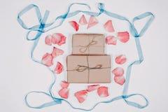 Zwei Geschenke inparchment mit den rosa Blumenblättern und blaues Band auf weißem Hintergrund Draufsicht, flache Lage Stockbilder