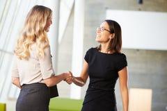 Zwei Geschäftsfrauen, die Hände im modernen Büro rütteln Stockfoto