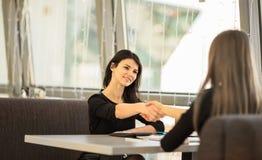 Zwei Geschäftsfrauen, die Hände rütteln Lizenzfreie Stockfotos