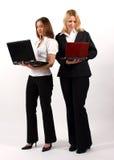 Zwei Geschäftsfrauen, die mit Laptopen stehen Stockbild