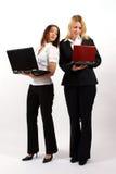 Zwei Geschäftsfrauen, die mit Laptopen stehen Stockfotos
