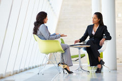 Zwei Geschäftsfrauen, die um Tabelle im modernen Büro sich treffen Lizenzfreie Stockfotografie