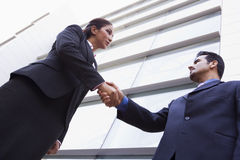 Zwei Geschäftsleute, die Hände außerhalb des Büros rütteln Lizenzfreie Stockfotos