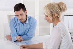 Zwei Geschäftsleute, die im Büro arbeitet in einem Team sitzen, schauen Stockbilder