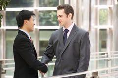 Zwei Geschäftsmänner, die Hände außerhalb des Büros rütteln Stockfotografie