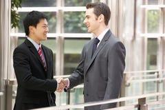 Zwei Geschäftsmänner, die Hände außerhalb des Büros rütteln Lizenzfreies Stockfoto