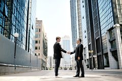Zwei Geschäftsmänner, die Hände auf Hintergrundbüro-Unternehmensgebäuden rütteln Stockfotografie
