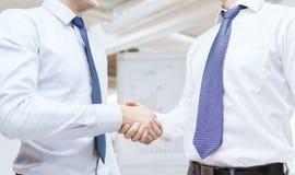 Zwei Geschäftsmänner, die Hände im Büro rütteln Lizenzfreies Stockfoto