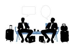 Zwei Geschäftsmänner, die im Flughafenaufenthaltsraum sprechen Stockbilder