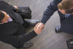 Zwei Geschäftsmänner, die zuhause Hände rütteln Stockfoto