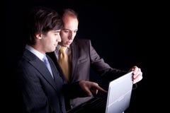 Zwei Geschäftsmänner, die zusammen an einem Laptop arbeiten Lizenzfreies Stockbild