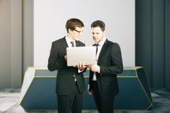 Zwei Geschäftsmänner unter Verwendung des Laptops zusammen Stockfotos