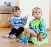 Zwei Geschwister, die auf Kammertöpfen sitzen Stockfotografie