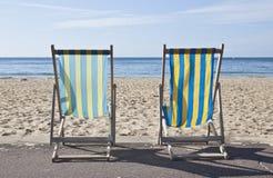 Zwei gestreifte Klappstühle, die das Meer gegenüberstellen Lizenzfreies Stockbild
