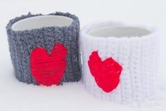 Zwei gestrickte Becher mit roten Herzen auf Schnee Stockfotografie