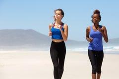 Zwei gesunde junge Frauen, die auf dem Strand laufen Stockfoto